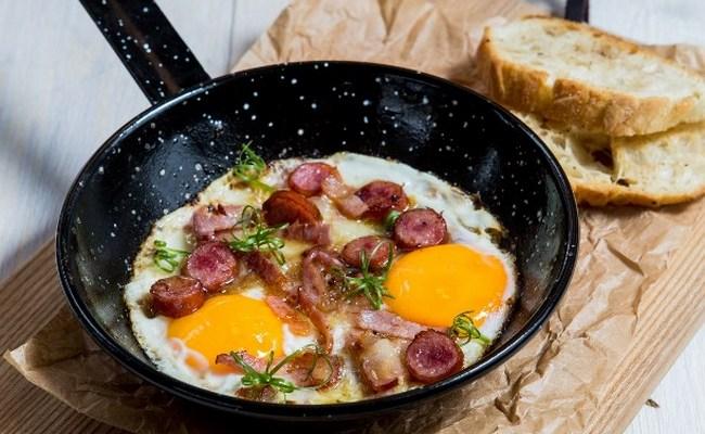 Яичница с охотничьими колбасками, помидорами и жареным луком